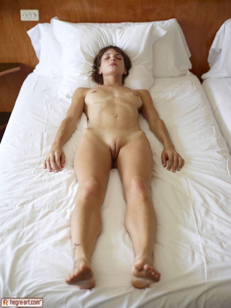 Брюнетка с упругим бюстом и верблюжьей лапкой на бикини спит на большой кровати, демонстрируя свое тело