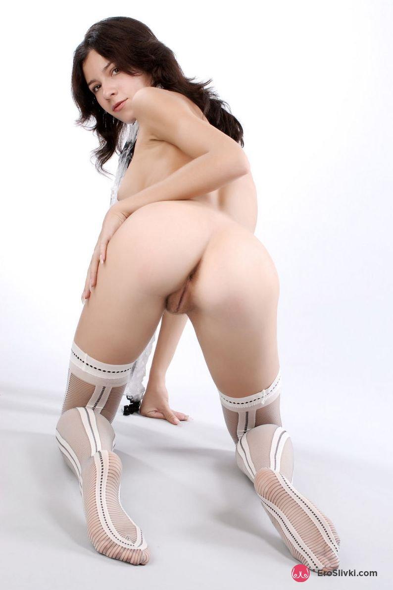 Русская темноволосая девка в милых носках эротично позирует обнаженной