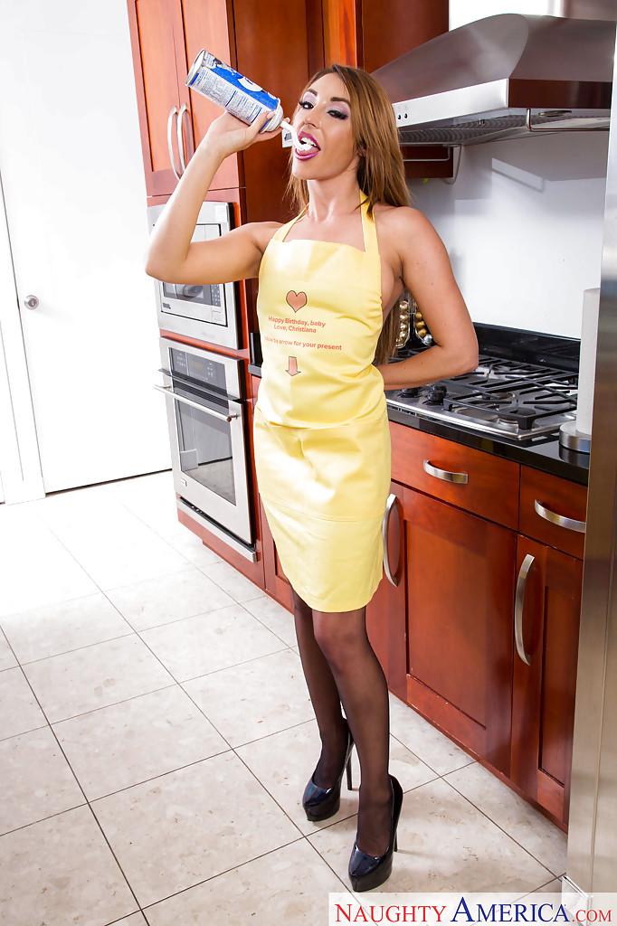 Уборщица хвастается на кухне в фартуке и черных гольфах